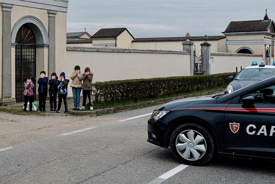 Дети зажмуриваются и закрывают лица руками — без согласия родителей их снимать запрещено. Прямо перед ними — автомобиль карабинеров, итальянской военной полиции, которая следит за порядком во время карантина. Школы в «красной зоне» закрыты, и уроки проходят в онлайн-формате: ученики получают и выполняют домашние задания через сеть.