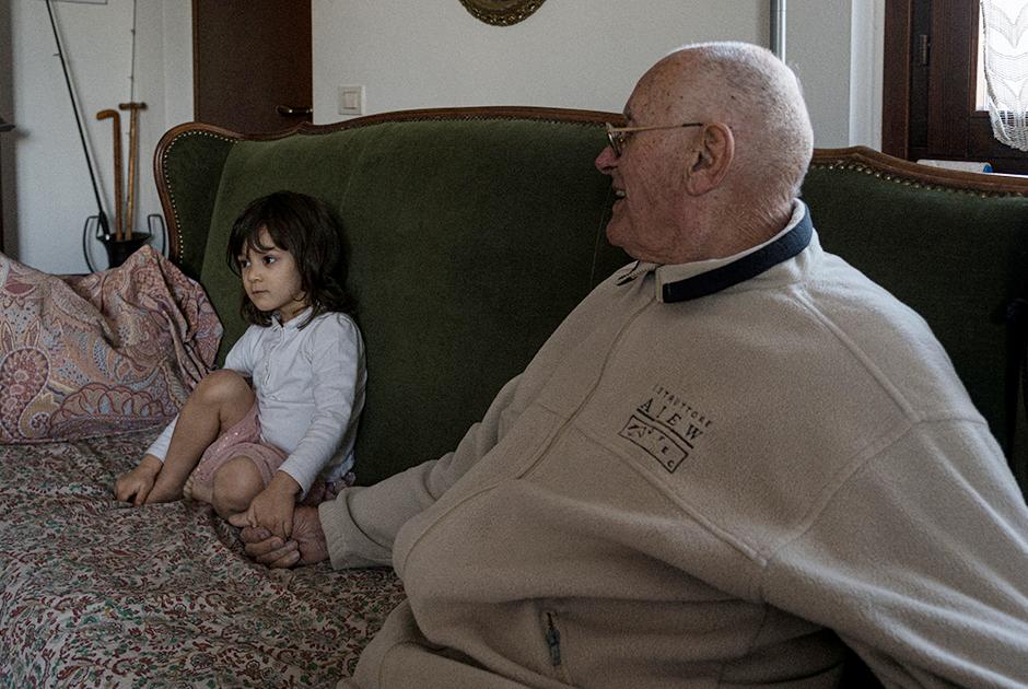 Двухлетняя Бьянка Тониоло (Bianca Toniolo) держит за руку дедушку, вместе они смотрят телевизор, по которому транслируют последние данные о вспышке коронавируса. Пару дней назад девочка не на шутку взволновала близких — им казалось, что у нее начался жар. Родственники несколько раз измеряли ребенку температуру, использовав целый набор термометров, и в конце концов, не обнаружив повышения, успокоились.