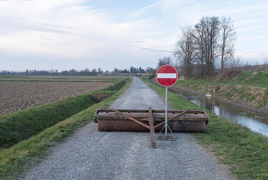 Сан-Фьорано — один из десятка крошечных городов на севере Италии, который уже третью неделю находится на карантине. Знак «въезд запрещен» и лежащий поперек грунтовой дороги тракторный каток — символы вынужденной изоляции.