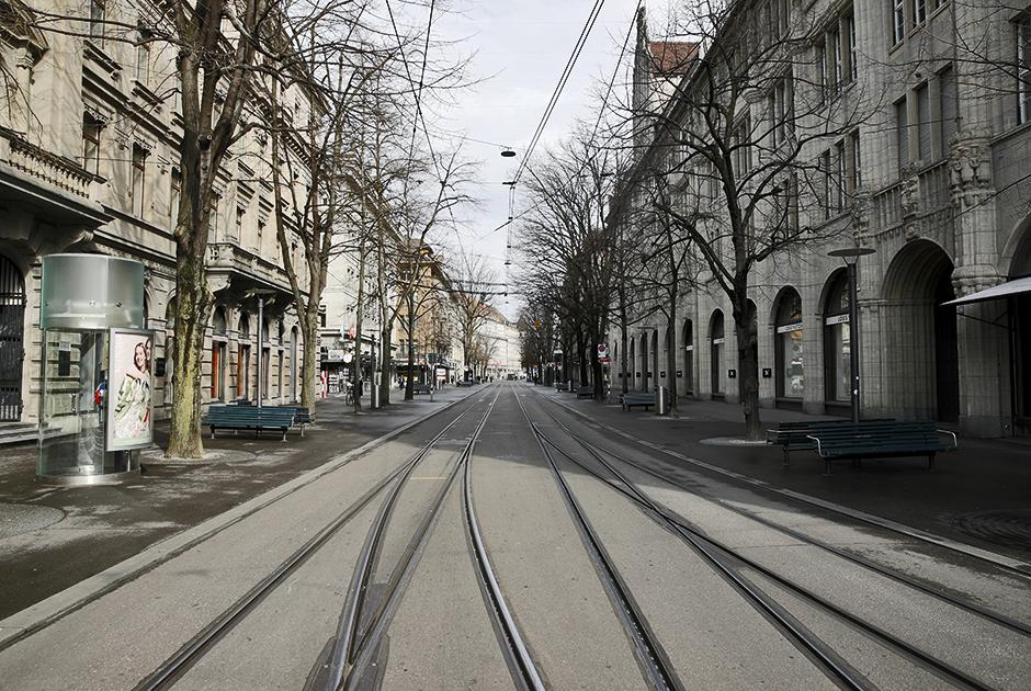 """Банхофштрассе в Цюрихе (Швейцария) — одна из <a href=""""https://lenta.ru/news/2019/11/14/streets/"""" target=""""_blank"""">самых дорогих</a> улиц мира. В 2011 году она <a href=""""http://www.swissinfo.ch/eng/business/bahnhofstrasse-rents-at-record-high/32083766"""" target=""""_blank"""">возглавила</a> аналогичный европейский рейтинг. Также Банхофштрассе является важным городским транспортным узлом. Однако теперь улица пустует, а магазины закрыты — в стране объявлен режим ЧС.<br><br>Всего в Швейцарии, по данным на 19 марта, заразилось более трех тысяч человек. Из них вылечились 15, а скончались 33 человека."""
