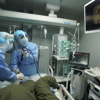Врачи возле пациента с коронавирусом SARS-CoV-2 в уханьской больнице