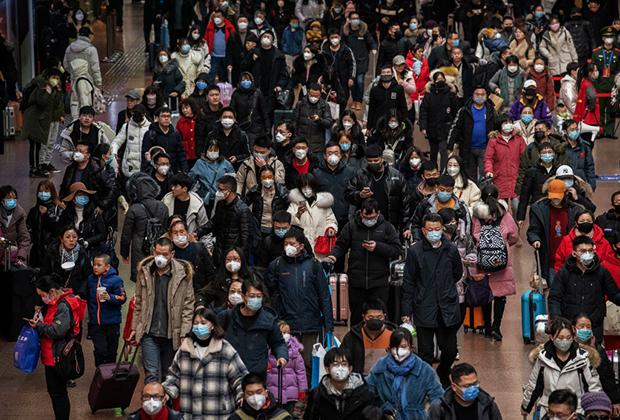 Пассажиры на железнодорожной станции в Пекине, путешествующие во время каникул в честь китайского Нового года