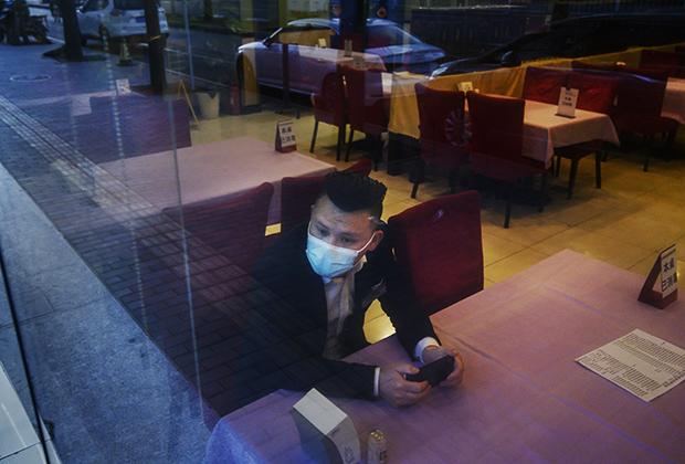 Официант в опустевшем пекинском ресторане