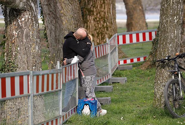 Влюбленная пара у появившегося из-за пандемии коронавируса забора на границе Германии и Швейцарии