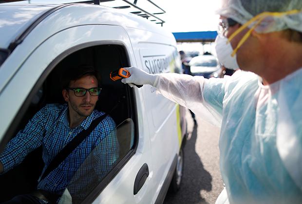 Медработник измеряет температуру у водителя в Буэнос-Айресе, Аргентина