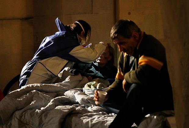 Волонтер помогает бездомному в Милане