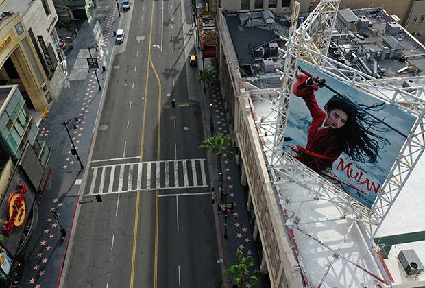 Постер фильма «Мулан», который должен был выйти на экраны 27 марта, на опустевшем из-за карантина Голливудском бульваре в Лос-Анджелесе