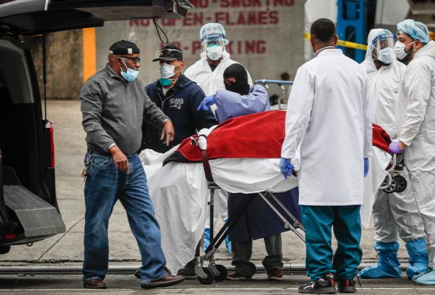 Медики в защитных масках транспортируют тело из временного морга на улице нью-йоркского Бруклина