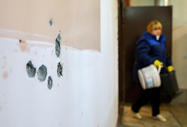 Места попадания пуль в стене на месте убийства в подъезде жилого дома
