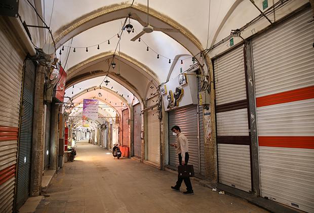 Мужчина в маске идет вдоль закрытых магазинов в иранском городе Кум
