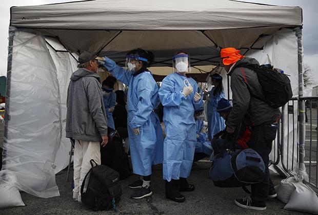 Студенты-медики измеряют температуру у бездомных из импровизированного лагеря на парковке в Лас-Вегасе, штат Невада