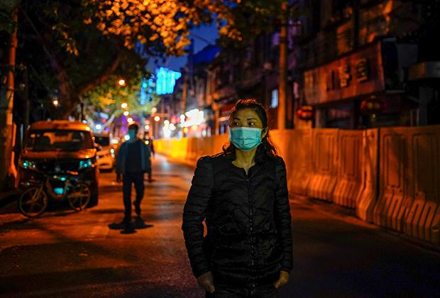 Женщина на улице Уханя 14 апреля 2020 года — через несколько дней после ослабления карантинных мер