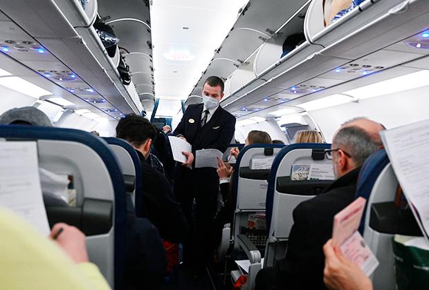 Бортпроводник в медицинской маске раздает анкеты пассажирам, прибывающим в Россию через аэропорт Шереметьево из стран с неблагополучной эпидемической обстановкой