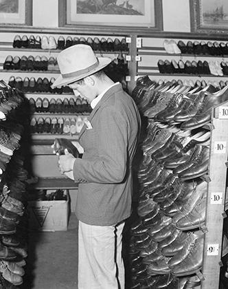 Окленд, Калифорния. Молодой иммигрант покупает шляпу и обувь в благотворительном комиссионном магазине The Oakland Salvation Army Store