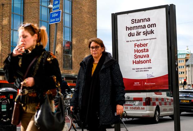 Вывеска-предупреждение в Стокгольме: «Оставайтесь дома, если вы больны. Признаки коронавируса — лихорадка, кашель, ринит, ангина»