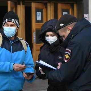 Сотрудники полиции проверяют цифровой пропуск у мужчины в Москве