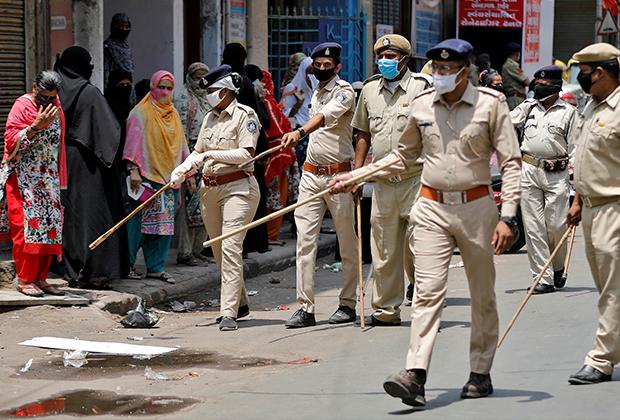 Полицейские советуют женщинам, стоящим в очереди за продуктами в Ахмедабаде, держать дистанцию