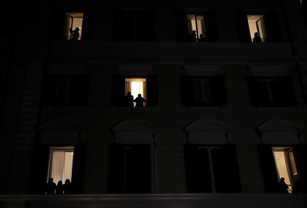 Люди смотрят из окон на приуроченную к 8 Марта демонстрацию женщин в Риме