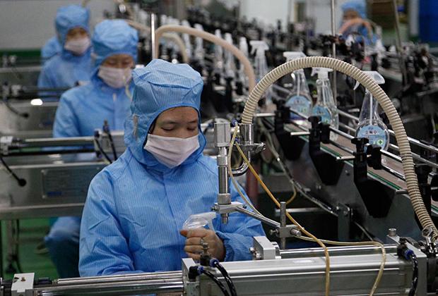 Работники производящего мыло завода разливают дезинфицирующую жидкость, Пхеньян