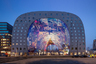 Жить на рынке неплохо, если это Market Hall в Роттердаме, Нидерланды. Это крытый фермерский рынок, стены и потолок которого представляют собой жилой дом на 228 квартир. Проект разработало архитектурное бюро MVRDV совместно с девелоперской компанией Provast. Под землей расположились паркинг на 1200 автомобилей и торговый центр. Все окна, согласно нидерландским строительным нормам, выходят на улицу, во двор— лишь окна служебных помещений. Это сделано для того, чтобы у жильцов было больше солнечного света. Все поверхности на рынке, кроме пола, покрыты произведениями художника Арно Коэнена.