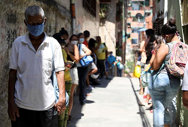 Очередь за получением бесплатной еды в трущобах Каракаса
