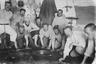 Акатуйская (Акатуевская) каторжная тюрьма — одна из тюрем Нерчинской каторги. С 1890 по 1911 год там содержались политические заключенные мужского пола, с 1911 года и до революции каторжная тюрьма была женской.  <br></br> На фото группа политкаторжан вяжет веники. На крайнем левом арестанте надеты ножные кандалы с подкандальниками и поджильниками (подкладки под кандалы, защищавшие кожу), а также сыромятным ремешком, позволяющим подвесить кандалы к поясу. <br></br> В тюрьмах Российской империи политическим арестантам, в отличие от уголовных, разрешалось не носить арестантскую одежду, поэтому в тюремную форму одет лишь один из заключенных — третий справа (по каким-то причинам он не воспользовался правом носить свою одежду). На нем суконная бескозырка, и ему же, скорее всего, принадлежит висящий на стене арестантский халат.