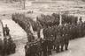 Надвоицкая детская трудовая колония (ДТК) была организована в 1939 году на базе отдельного лагерного пункта Беломор-Балтийского ИТЛ, куда направлялись несовершеннолетние. Воспитанники колонии работали главным образом на Надвоицкой мебельной фабрике. <br></br> На фото— несколько колонн воспитанников ДТК, одетых в брюки, гимнастерки без знаков различия и пилотки. Крайняя левая колонна стоит под знаменем пролетарского спортивного общества «Динамо».  <br></br> На переднем плане— группа офицеров, сержантов и рядовых сотрудников колонии. Видны награды за участие в боях Великой Отечественной войны. Погоны для сотрудников ИТЛ были введены в апреле 1943 года — вскоре после их появления в Красной армии (январь 1943). <br></br> Надвоицкую ДТК ликвидировали 18 декабря 1959 года.