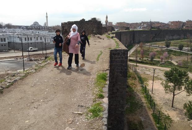 Курды на крепостной стене Сура на фоне новостроек