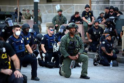 Полицейские встали на колени перед протестующими в США