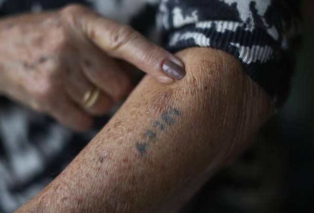 Узница концлагеря показывает татуировку с ее номером. Лондон, 2014 год