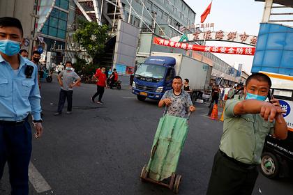 Люди и охранники перед закрытым рынком в Пекине