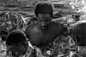 Беженец, спасенный судном организации Mediterranea, сбрасывает с себя термоодеяло. Он был одним из 98 потерпевших кораблекрушение, которых подобрало судно «Маре Джонио» в 113 километрах от ливийского города Мисурата. Большинство мигрантов подвергались пыткам в своей стране.  <br> <br> Группа беженцев покинула Ливию и двое суток плыла в надувной лодке, пока ее двигатели не отказали. Шлюпка начала сдуваться, погибли шесть человек. На помощь пришел «Маре Джонио», людей спасли, однако бывший министр внутренних дел Италии Маттео Сальвини запретил судну заходить в итальянские воды, из-за чего ему пришлось много дней простоять в море в 24 километрах от острова Лампедуза.  <br> <br> 29 августа 2019 года корабль береговой охраны Италии взял на борт 64 мигранта. Пересадка осуществлялась ночью в открытом море при сильном волнении, отчего всю операцию окрестили позорной. Судно «Маре Джонио», приняв 34 мигранта, провело в море шесть дней. Люди находились в антисанитарных условиях при отсутствии питьевой воды. По прошествии шести дней руководитель миссии заявил: «Братья и сестры, мы победили». Последние 34 человека, оставшиеся на борту судна, были наконец эвакуированы.