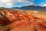 Одну из горных долин на Алтае заслуженно называют местным Марсом — неподалеку от Чуйского тракта там раскинулась долина Кызыл-чин, скалы которой пестрят красными, коричневыми, золотистыми и рыжими оттенками. Такая необычная «марсианская» палитра объясняется богатым наличием марганца и хрома, а также примесей кварца, рутила, халцедона, серного колчедана и других минералов и полиметаллических руд. Этими «красками» умело орудовали ветер и вода — они формировали из гор стены и настоящие колоннады, прорезали бороздки и овраги.