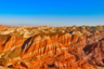 Красочные скальные формирования Чжанъе Данксиа в китайской провинции Ганьсу напоминают палитру с акварелью — раскрашенные в пастельные тона горы как будто расписаны рукой умелого живописца. Образовались они сотню миллионов лет назад: тогда в крупный природный бассейн водой занесло ил, который вместе с осадком под воздействием высоких температур высох, окислился и приобрел рыжевато-красный цвет. При этом толщина цветного слоя со временем увеличивалась и постепенно достигла почти четырех километров.