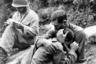 Американский пехотинец плачет на плече товарища после гибели своего друга. В это время санитар (на снимке — слева) занимается документальным оформлением боевых потерь. 28 августа 1950 года.