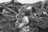 Пожилая женщина с внуком на руинах своего дома после налета американской авиации. Пхеньян, Северная Корея, 1950 год.