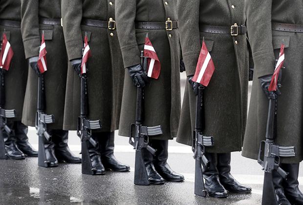 Ленты в цветах национального флага у солдат армии Латвии. Парад в честь Дня независимости