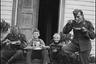 Военнослужащие люфтваффе во время обеда и дети, сидящие на крыльце с игрушечным самолетом в руках. Аэродром Тронхейм Варнес, Норвегия, 1940 год.