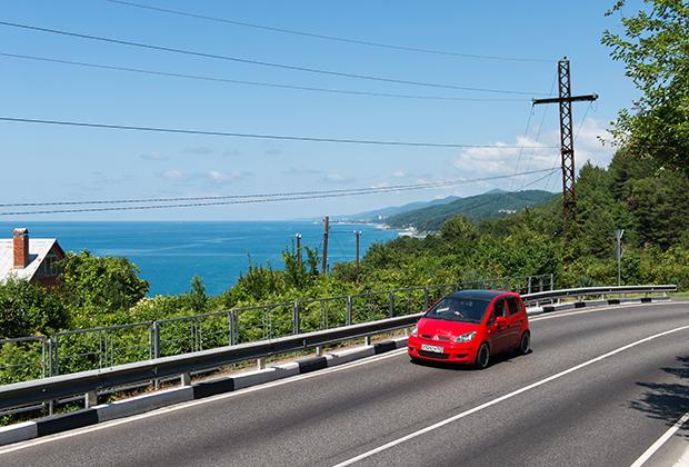 Машина на автомобильной дороге Джубга — Сочи (А-147). Это единственная дорога между Джубгой и Сочи, заканчивающаяся на границе с Абхазией, протяженностью 170 километров по горному серпантину