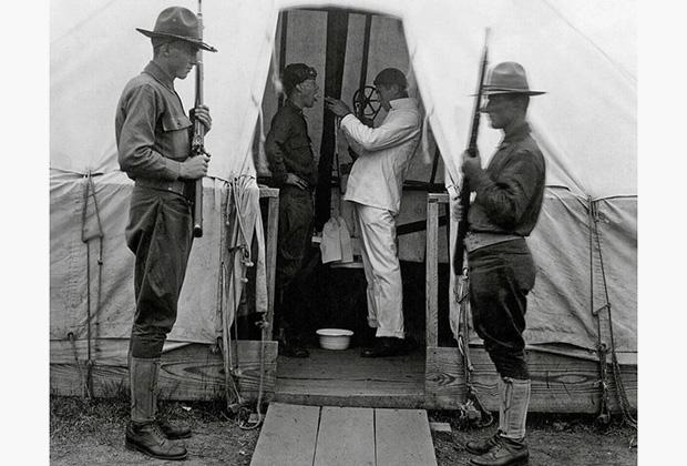 1918 год, США. Врач осматривает горло пациента в военном лагере