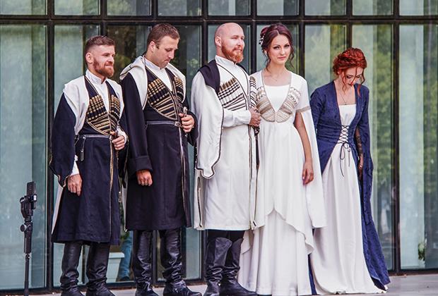 Жених и невеста в традиционных свадебных нарядах позируют возле Дома Юстиции в Тбилиси, 2019 год