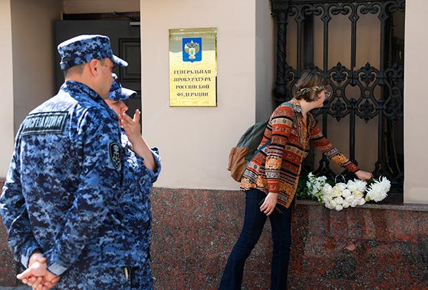 Девушка возлагает цветы в знак поддержки сестер Хачатурян у здания Генпрокуратуры