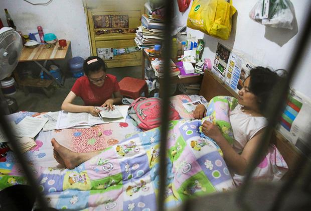 Школьница делает домашнее задание на кровати, где лежит ее мать, в Маочантане