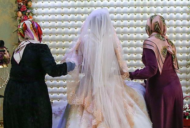 Невесту ведут на место, где она будет стоять все время празднования чеченской свадьбы