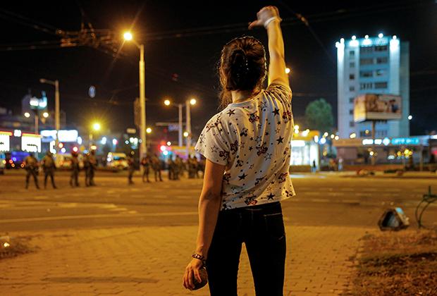 Женщина наблюдает за разгоном митинга 10 августа