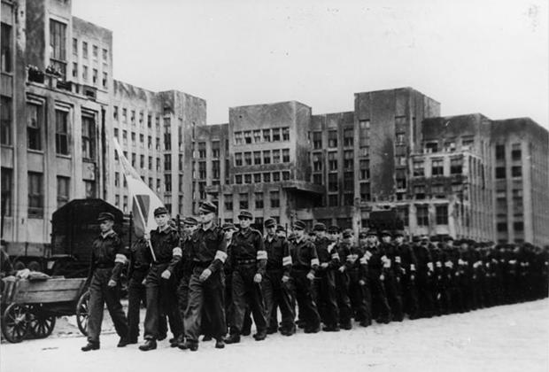 На пути к железнодорожному вокзалу в Минске возле нынешнего Дома правительства молодежь из Беларуси марширует мимо профессора Островского. Они должны быть обучены в Германии для военных действий.