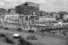 """Первая московская послевоенная ярмарка <a href=""""https://www.mos.ru/news/item/15310073/"""" target=""""_blank"""">состоялась</a> в 1947 году. Она ознаменовывала восстановление экономики и подъем промышленности, а также дарила людям приятные и яркие эмоции после тяжелых лет. Весенний базар стал символом возвращения города к нормальной жизни.<br><br>Кадр сделан с Тверской улицы (в те годы — улицы Горького). Там, где на снимке стоят арки-декорации, сейчас находится памятник Александру Пушкину. На заднем плане — конструктивистское <a href=""""https://ru.wikipedia.org/wiki/Здание_газеты_«Известия»"""" target=""""_blank"""">здание газеты «Известия»</a>, являющееся объектом культурного наследия. Редакция переехала в новый офис только в 2011 году, проработав здесь почти столетие."""