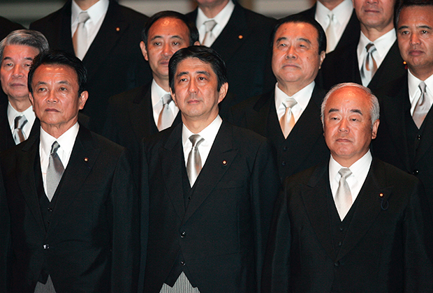 Shinzo Abe, circondato dai ministri nel 2006.  Yoshihide Suga sta dietro la sua spalla destra.