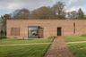 Над этим сельским пристанищем в английском графстве Девон поколдовал архитектор Маклин Куинлан. Он сделал из фрагмента старой кирпичной ограды настоящий пассивный (то есть энергосберегающий) дом, вдохнув новую жизнь не только в саму стену, но и в окружающий ее сад. Дизайн прост и чист: особняк выстроен за традиционным кирпичным фасадом, дополняющим кирпичную кладку садовой стены.<br><br>В центре дома есть зимний сад под стеклянной крышей, которая обеспечивает сбалансированное освещение комнат. В здании можно жить, также оно идеально подходит для проведения небольших выставок.