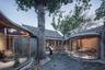 Это тоже результат переработки. Дом с изогнутыми стеклянными стенами создали на месте заброшенного пекинского хутона — так в Китае называют небольшие группы домов. Семь деревянных построек отремонтировали и объединили в одно домовладение. Архитекторы сохранили оригинальные материалы и добавили современные элементы, в том числе арочное остекление вокруг внутреннего двора. В доме есть две чайные комнаты, кабинет, столовая и гостиная, расположенные вокруг дворов, защищенных деревянными крышами.